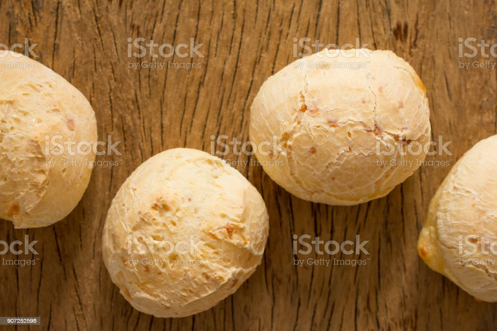 Pao de Queijo is a cheese bread ball from Brazil. Also known as Chipa, Pandebono and Pan de Yuca. Group of snacks on rustic wood, flat lay design. stock photo