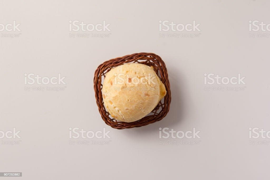 Pao de Queijo is a cheese bread ball from Brazil. Also known as Chipa, Pandebono and Pan de Yuca. One snack in basket over white background, minimalism. stock photo