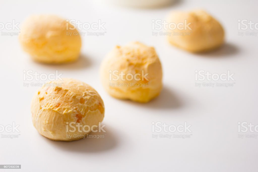 Pao de Queijo is a cheese bread ball from Brazil. Also known as Chipa, Pandebono and Pan de Yuca. Snacks spread over white table. Minimalism and selective focus. stock photo