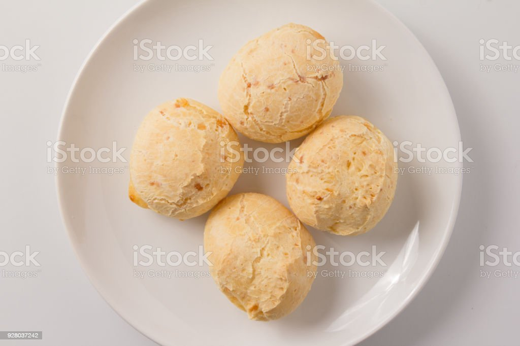 Pao de Queijo is a cheese bread ball from Brazil. Also known as Chipa, Pandebono and Pan de Yuca. Snacks over white plate, minimalism. stock photo