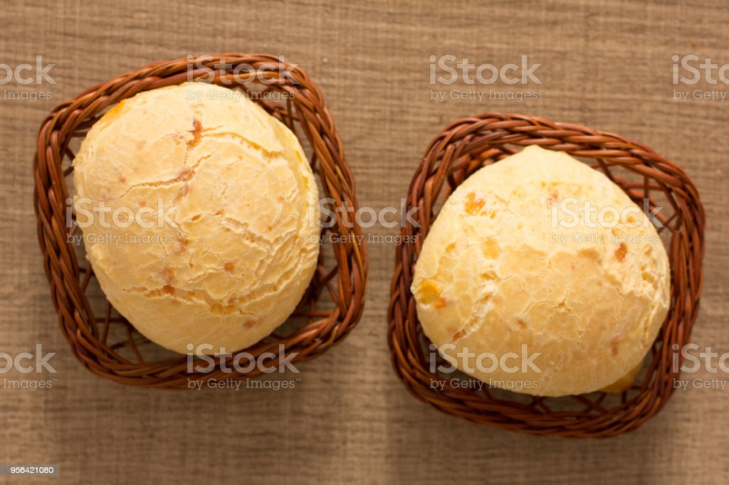 Pao de Queijo is a cheese bread ball from Brazil. Also known as Chipa, Pandebono and Pan de Yuca. Two snacks in basket over wood table, flat lay. stock photo
