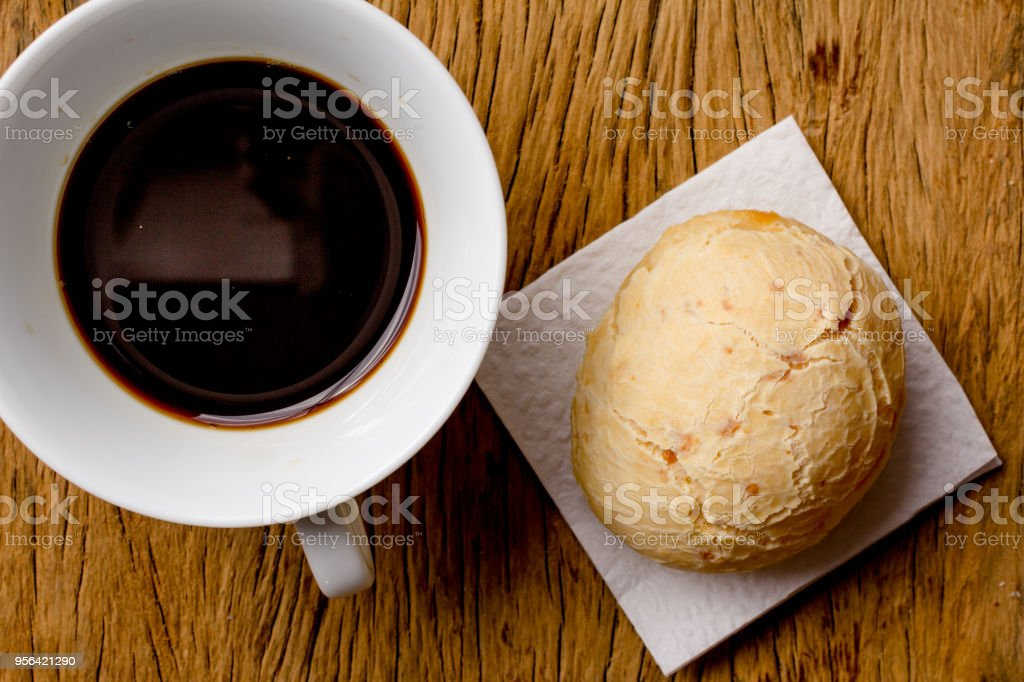 Pao de Queijo is a cheese bread ball from Brazil. Also known as Chipa, Pandebono and Pan de Yuca. Snack and espresso coffee on rustic wood, flat design. stock photo