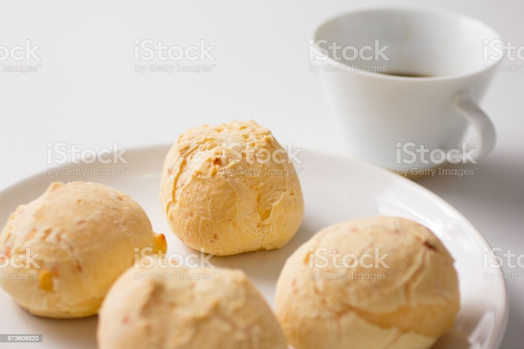 Pao de Queijo is a cheese bread ball from Brazil. Also known as Chipa, Pandebono and Pan de Yuca. Snacks on white plate and cup of coffee. stock photo