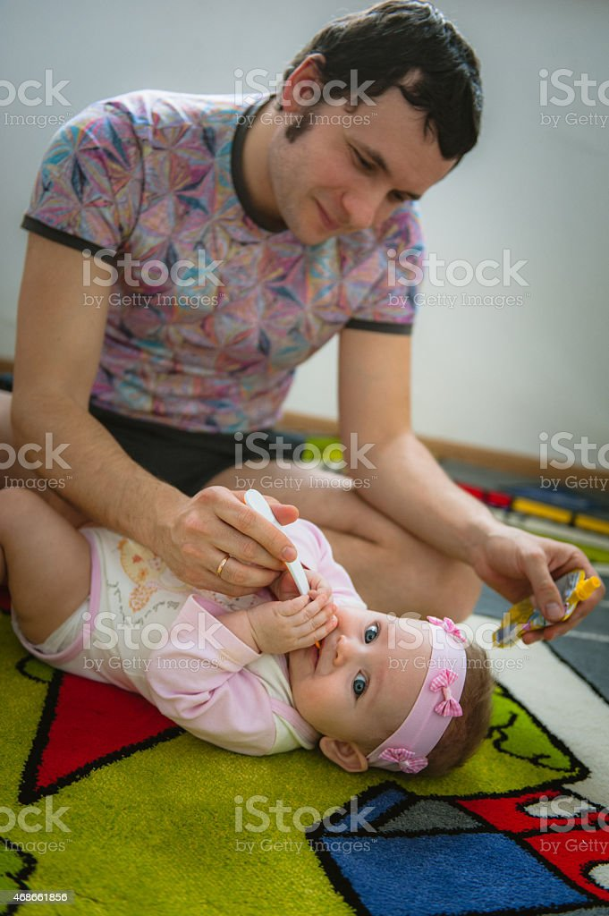 Papa feeds child with spoon stock photo
