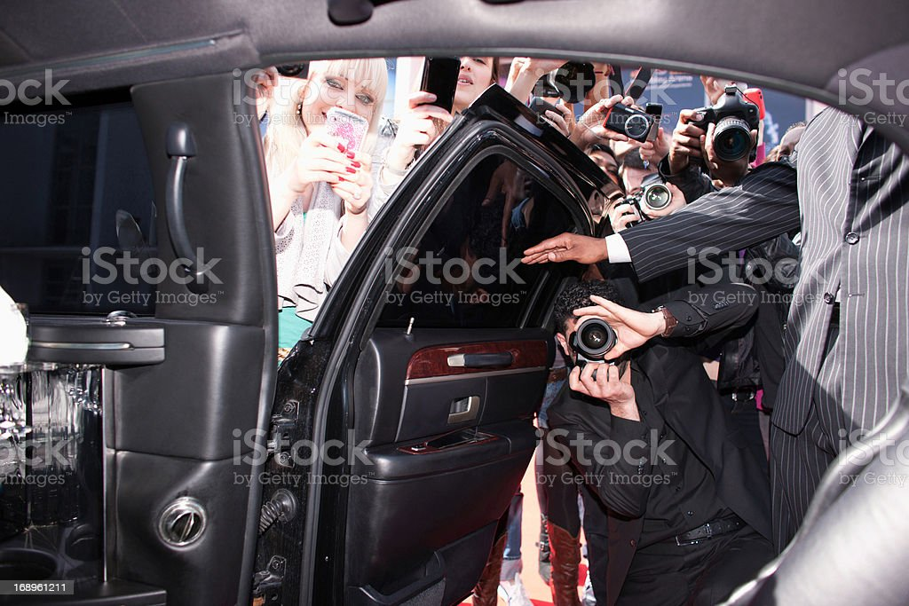 Paparazzi and fans taking photos inside car door stock photo