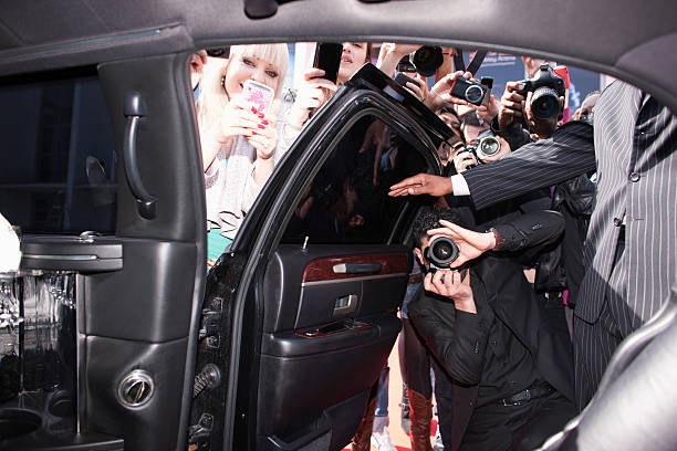 paparazzi and fans taking photos inside car door - fame stock photos and pictures