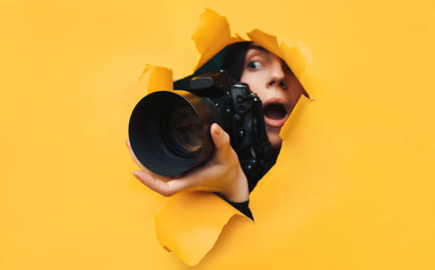 A paparazzi girl with a black reflex camera looks out from cover and looks at what is happening with her mouth open. Tabloid press. In search of the plot for photo stocks. A paparazzi girl with a black reflex camera looks out from cover and looks at what is happening with her mouth open. Yellow paper, torn hole. Tabloid press. In search of the plot for photo stocks. ambush stock pictures, royalty-free photos & images