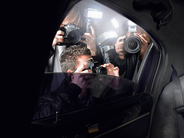paparazzi shooting through car window - fame stock photos and pictures