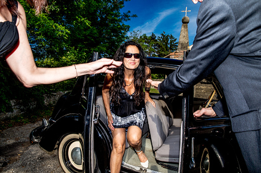 Paparazzi style portrait of two VIP woman exiting the vintage car with a Chauffeur