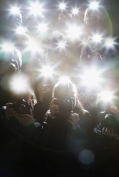 paparazzi taking pictures with flash - fame stock photos and pictures