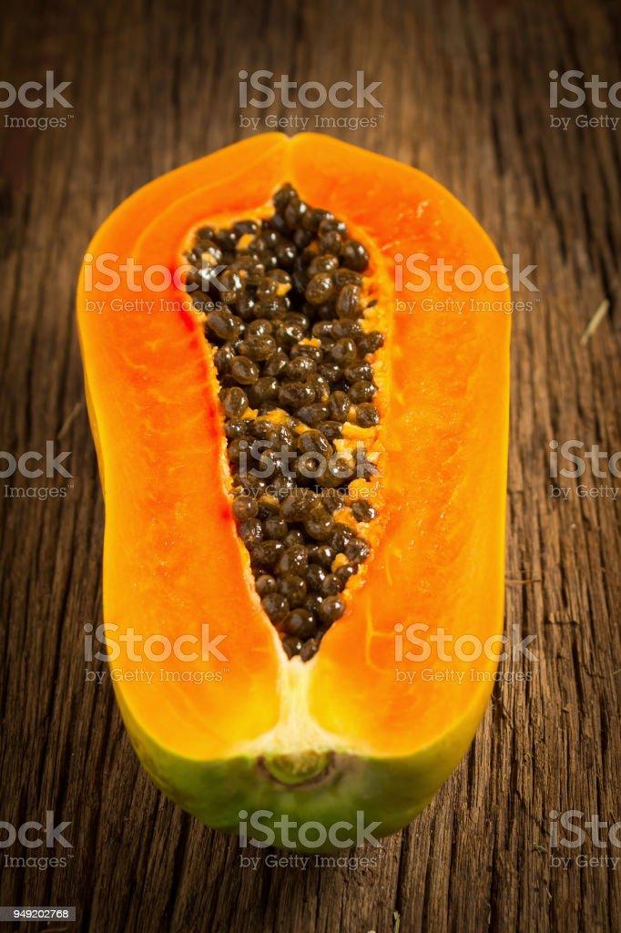 papaya fruit. half. seed. old wooden. moring. sunset. art. asian stock photo