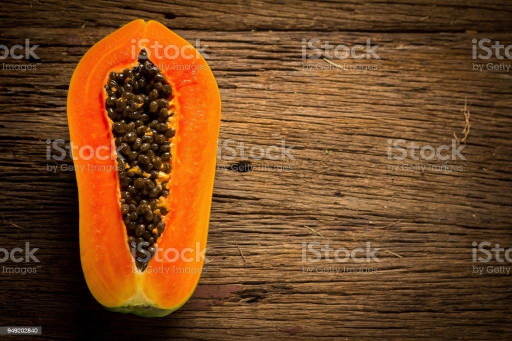 papaya fruit. half. seed. old wooden. moring. sunset. art. asian. top view stock photo
