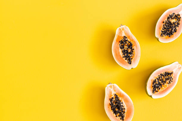Papaya on yellow background. Summer concept. Flat lay, top view, copy space stock photo