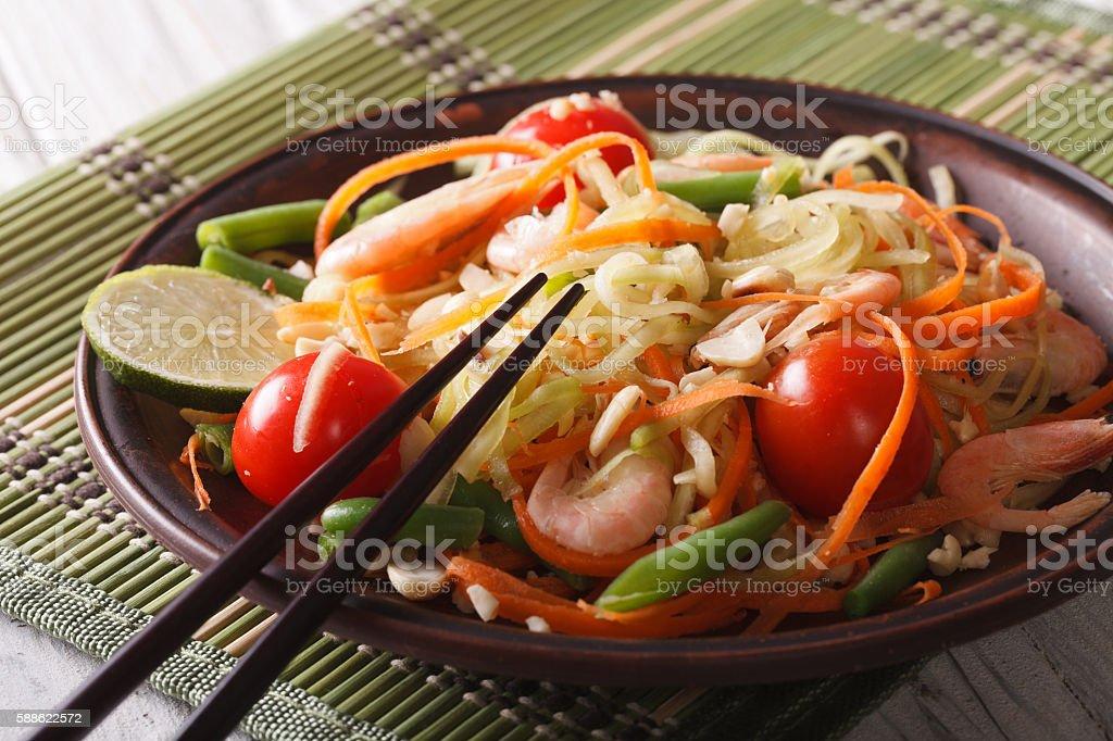 Papaya salad som tam with shrimp close-up on a plate stock photo