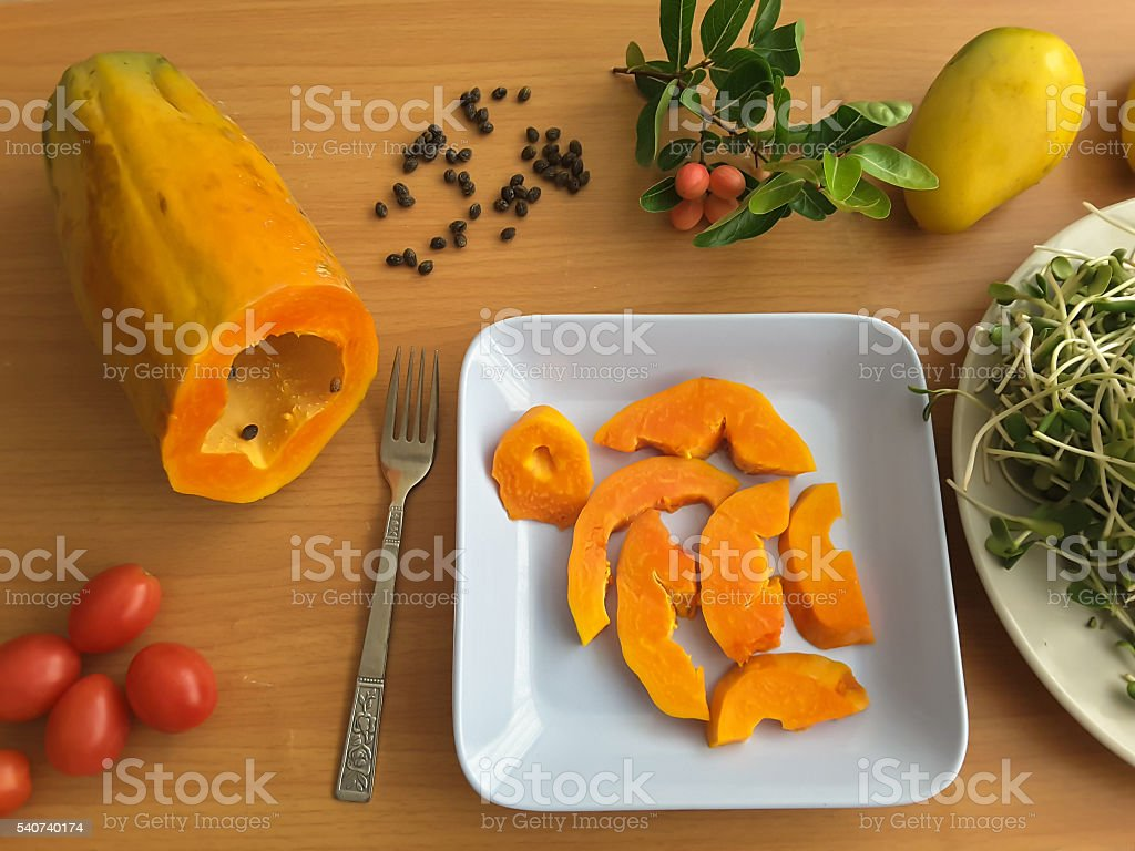 Papaya slices on plate, mango and tomatoesm on table стоковое фото