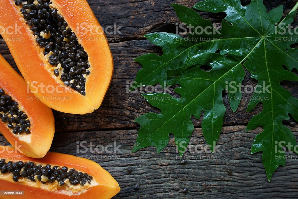 papaya with green leaf on old wooden background. stock photo