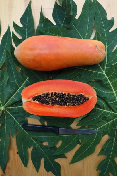 papaya_fruit_cut_half_with_knife_d stock photo