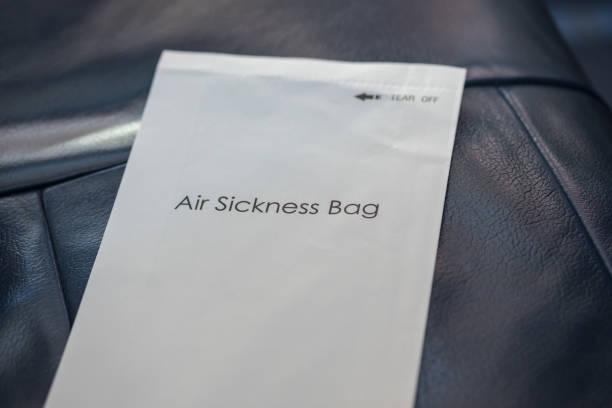 papiertüte luft krankheit auf airplne sitz - windbeutel stock-fotos und bilder