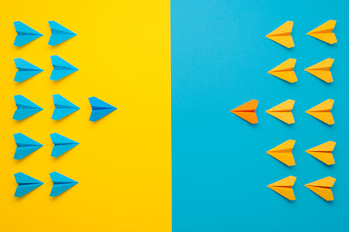Paper airplanes teamed up in 2 colors, blue and yellow, face to face in battle formation. A confrontation between two teams, leading the team concept.