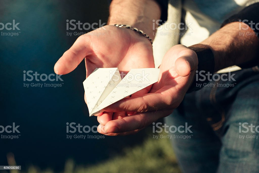 Paper airplane in male hands close-up - Photo