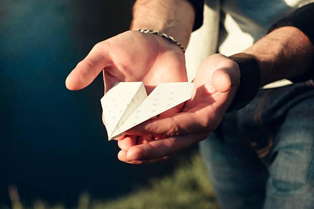 paper airplane in male hands close-up - flyer inspiration stock-fotos und bilder