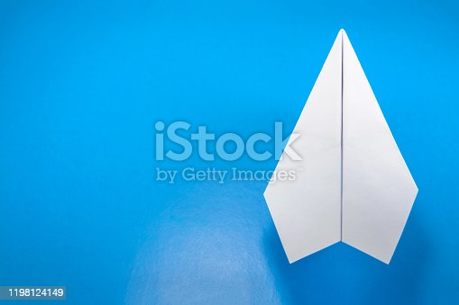 658921430 istock photo paper airplane made of white paper on a light blue background 1198124149