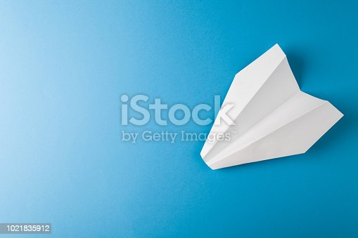 istock Paper airplane on a blue paper background 1021835912