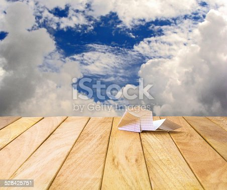 istock Paper airplane on a wooden platform. 528425751