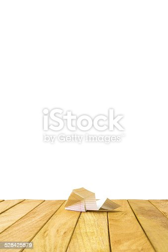 istock Paper airplane on a wooden platform 528425879
