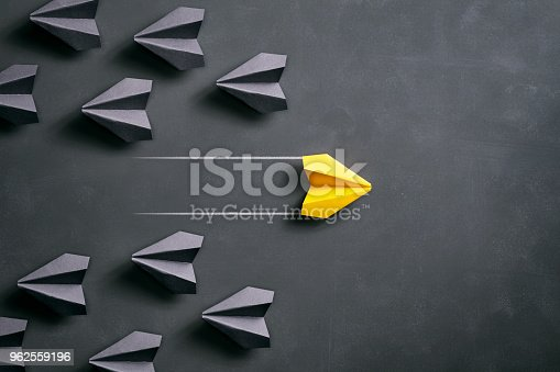 Conceptual photography with black and yellow paper airplanes on a smudged blackboard.