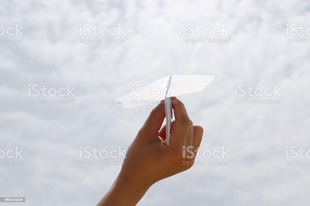 A paper airplane with hand of woman on blue sky. A concept of dreams and passion. royalty-free stock photo
