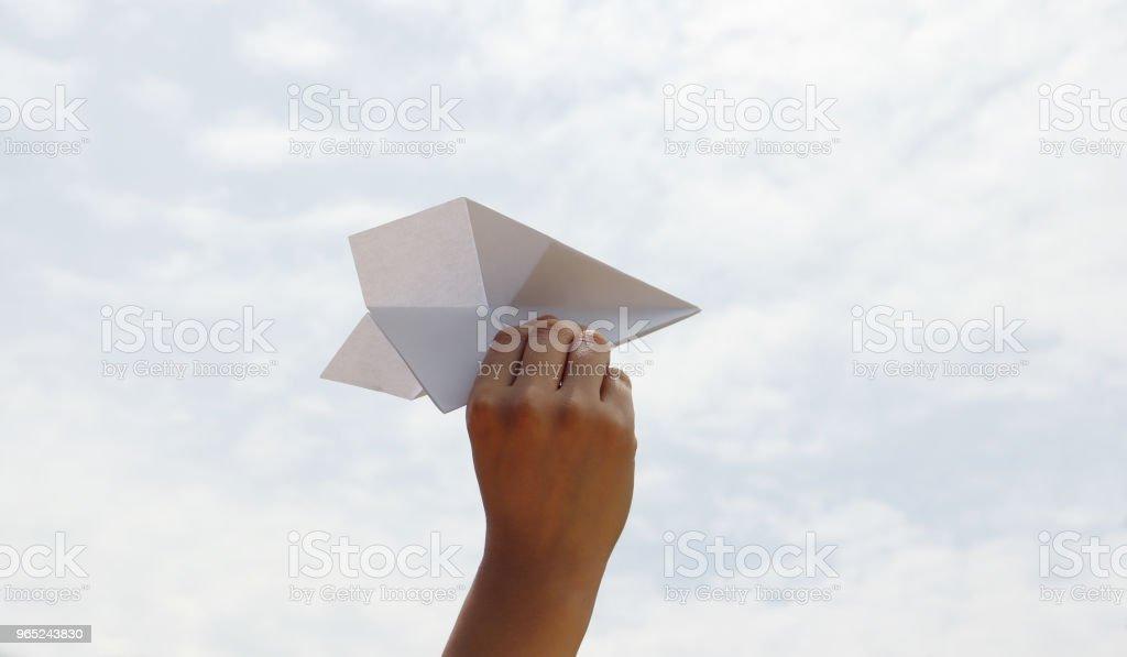A paper airplane with hand of woman on blue sky. zbiór zdjęć royalty-free