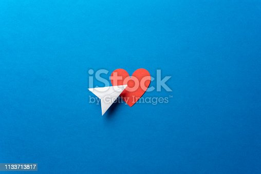 istock Paper airplane with red heart shape on blue background. Sharing and send symbol concept. Airplane flight transport sign. Landing page concept. 1133713817
