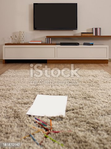 istock Paper and pencils on rug of modern living room 181870142