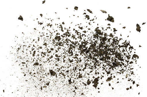 Closeup of black burnt paper ash dispersed on white background
