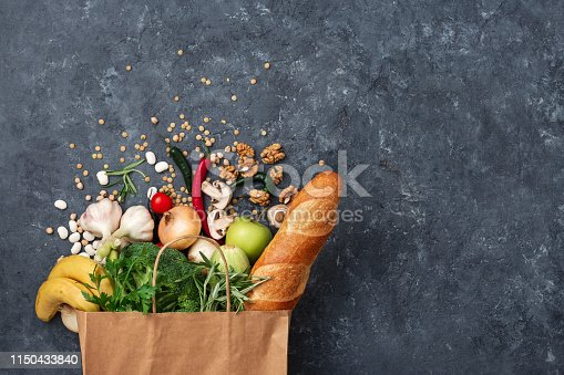 1126188273 istock photo Paper bag food with vegetables and fruit on dark background with copy space top view 1150433840