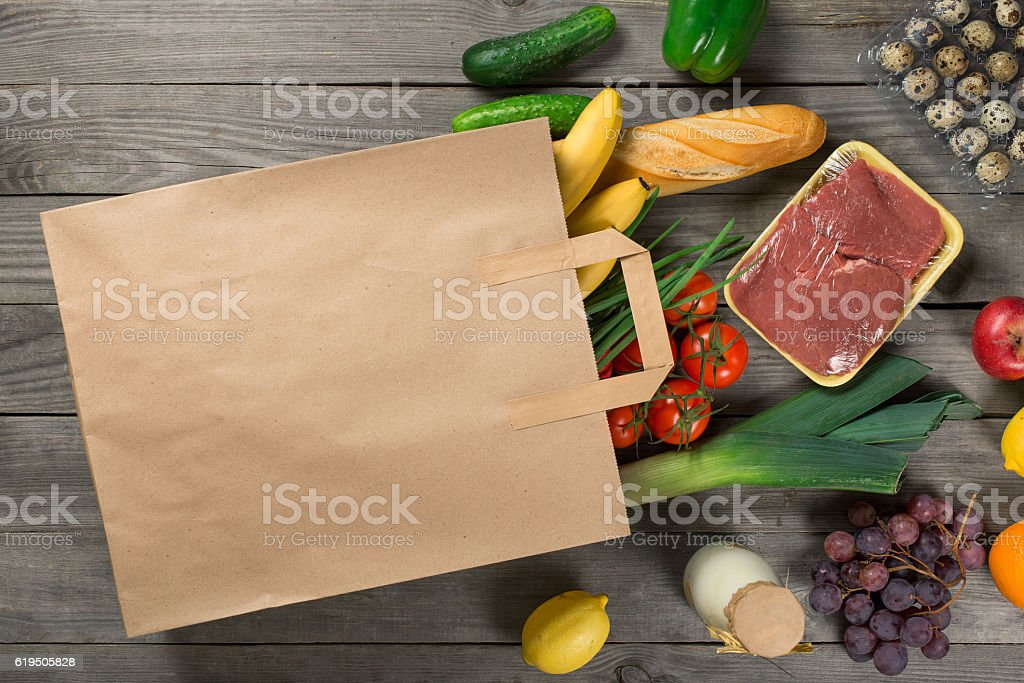 Paper bag full of different groceries on wooden background stock photo