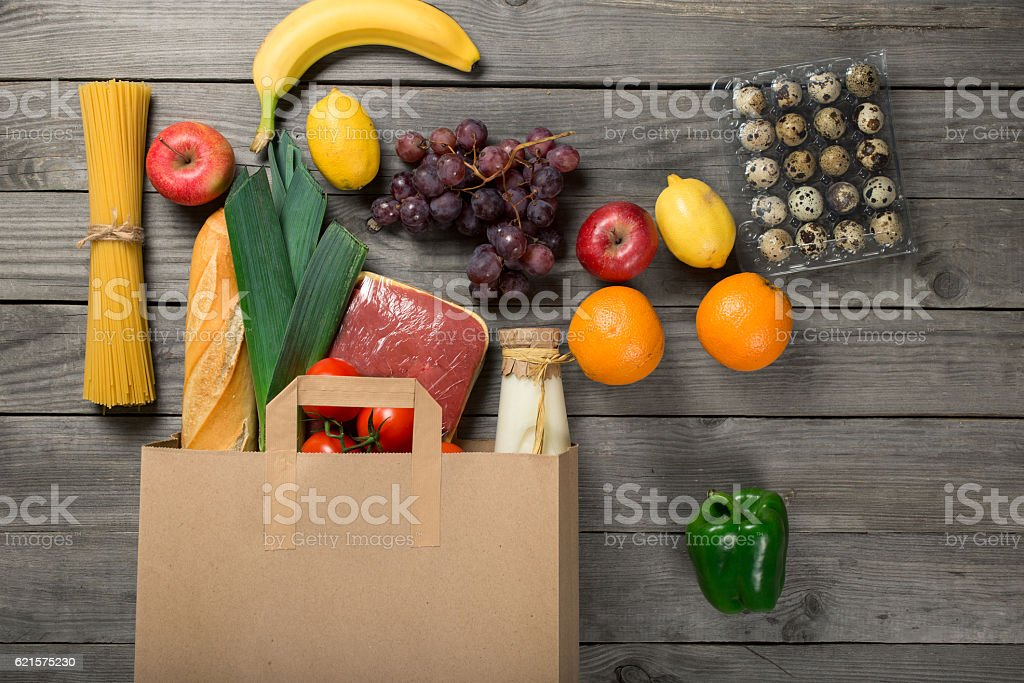 Paper bag full of different groceries on wooden table photo libre de droits