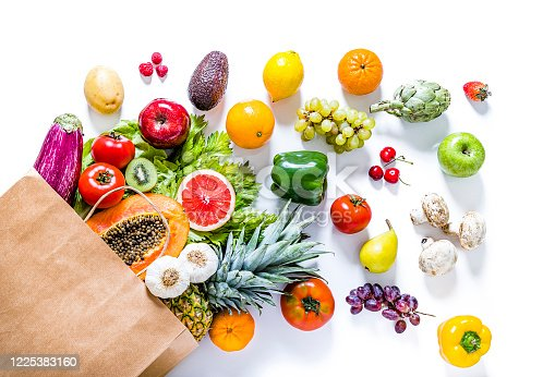 Top view of a paper bag full of various kinds of multicolored fruits and vegetables like papaya, tomatoes, red and green apples, carrots, mushrooms, eggplants, pineapple, cherries, lime, garlic, oranges and kiwi. The paper bag is laying at the lower left corner on a white background and the fruits and vegetables are coming out from it.  Studio shot taken with Canon EOS 6D Mark II and Canon EF 24-105 mm f/4L.