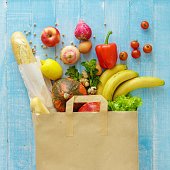 istock Paper bag of different health food on blue wooden background. Top view. Flat lay 902812600