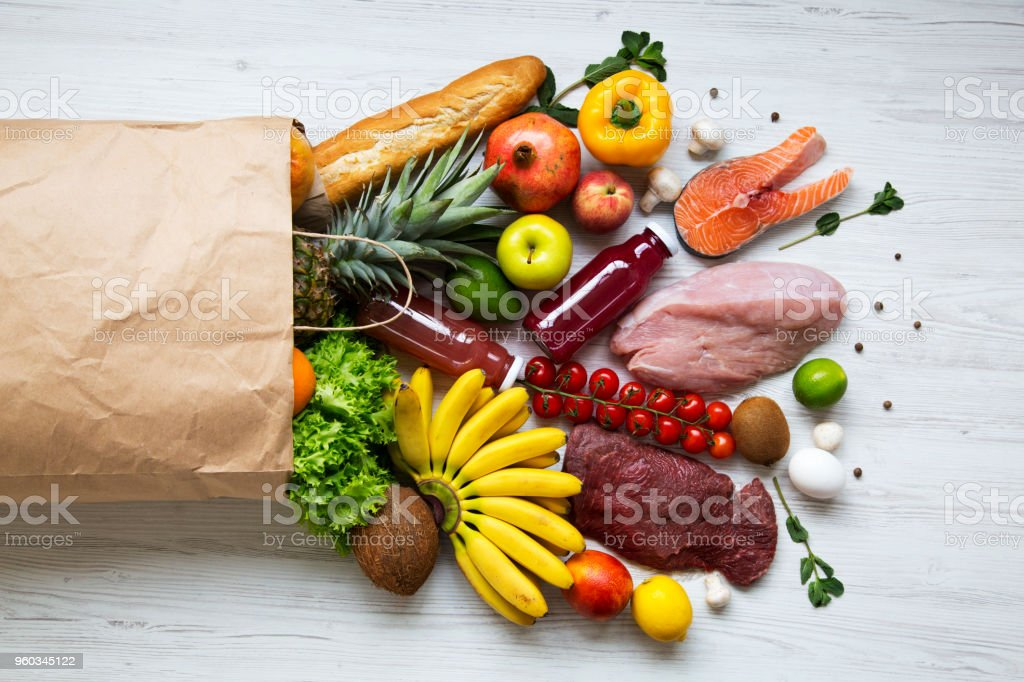 Paper bag of healthy products on white wooden background, top view. Health food. Flat lay. From above. stock photo
