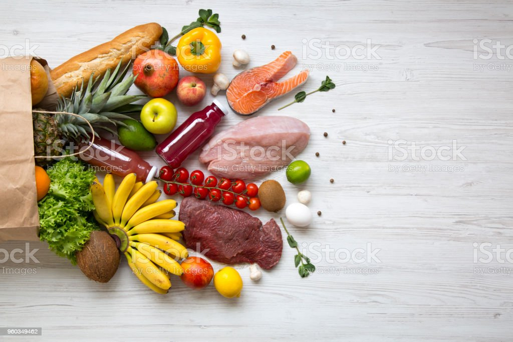 Paper bag of healthy raw food on white wooden table. Cooking food background. Flat-lay of fresh fruits, veggies, greens, different meat, top view, copy space. Shopping concept. stock photo