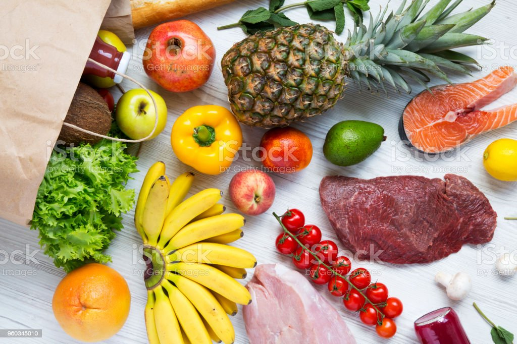 Paper bag of various health food on white wooden table. Healthy food background, top view. Healthy eating. stock photo