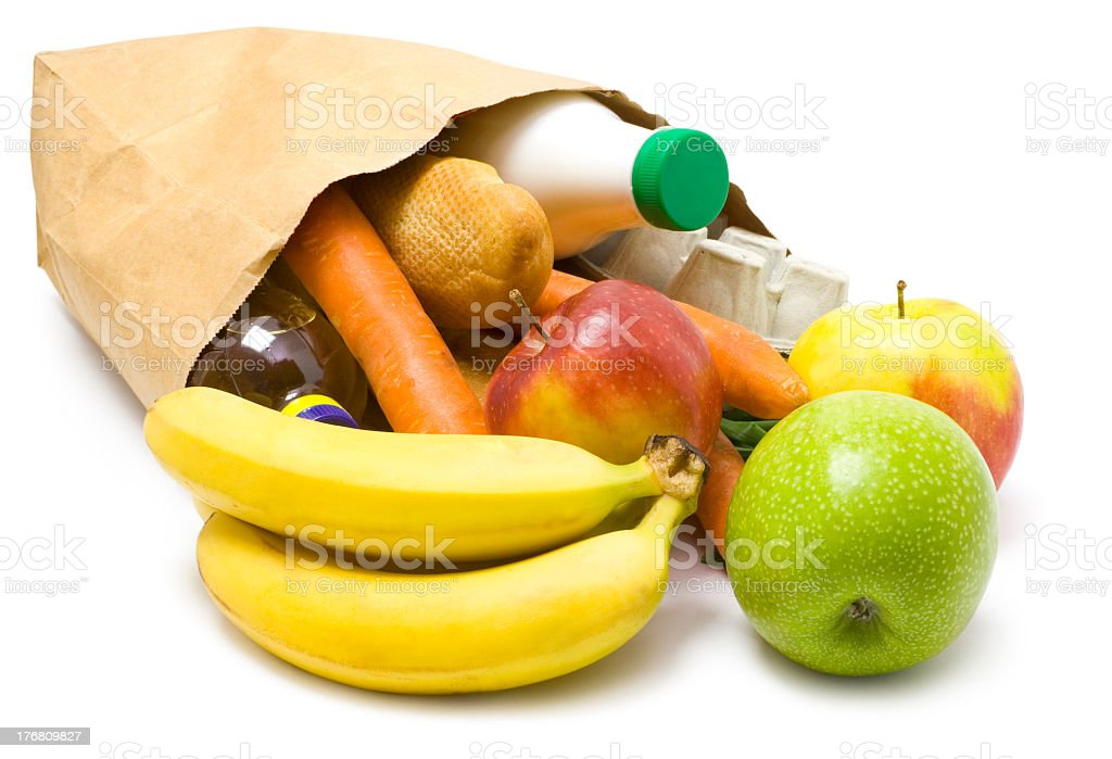 Paper bag on its side with fruit and vegetables spilling out royalty-free stock photo