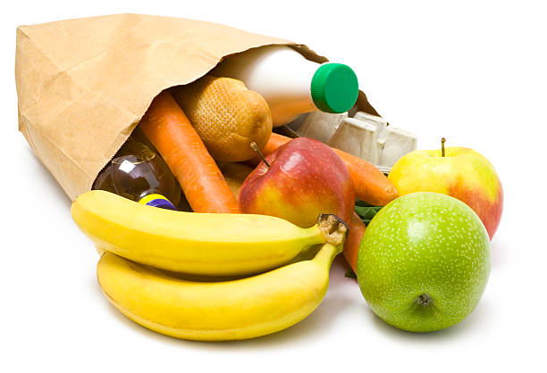 Paper bag on its side with fruit and vegetables spilling out stock photo
