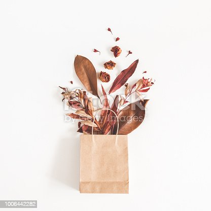 istock Paper bag with autumn flowers leaves. Flat lay, top view 1006442282