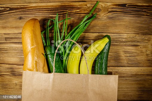 1126188273 istock photo Paper bag with different food on wooden table. Top view. Grocery shopping concept 1211629246