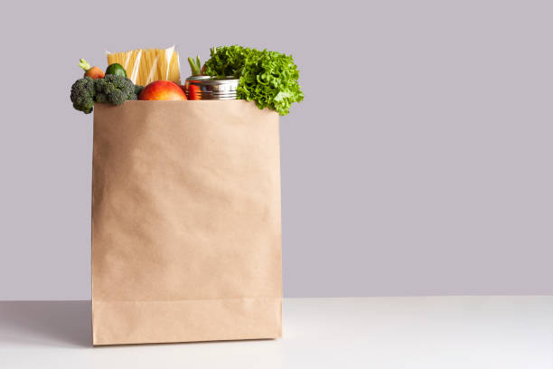 Paper bag with food gray background Various grocery items in paper bag on white table opposite gray wall. Bag of food with fresh vegetables, fruits, pasta and canned goods. Food delivery, shopping or donation concept. Copy space. groceries stock pictures, royalty-free photos & images