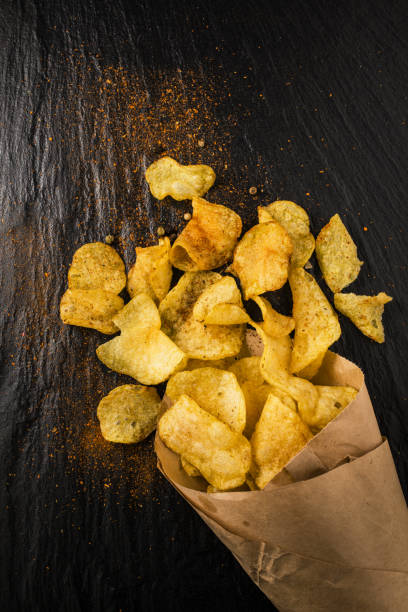 paper bag with spicy fries paper bag with fries and spices on a slate stone patatine fritte stock pictures, royalty-free photos & images