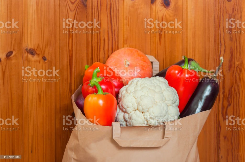 Paper bag with vegetables on wooden background. Selective focus. View...